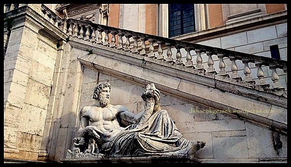 Kolunun altında dişi kurttan süt emen Romus ve Romulus heykeli var.
